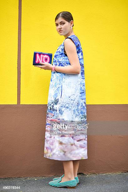 Elvira Abasova poses wearing a Natali Lescova coat and a Jimmy Choo clutch after the Marni show during the Milan Fashion Week Spring/Summer 2016 on...