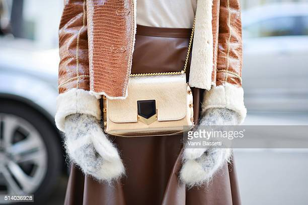 Elvira Abasova poses with a Jimmy Choo bag after the John Galliano show at the Lycee Carnot during Paris Fashion Week FW 16/17 on March 6 2016 in...