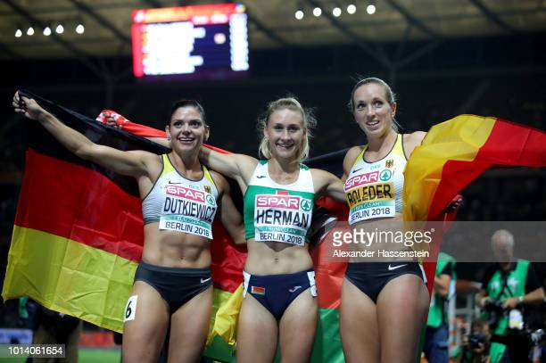 Elvira Herman of Belarus celebrates winning Gold with Silver medalist Pamela Dutkiewicz of Germany and Bronze medalist Cindy Roleder of Germany in...