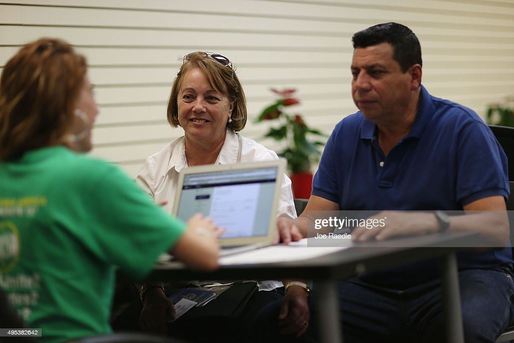 Elvira Lopezto (C) and Pedro Salavarria Carrasco (R) speak with Helen Alvarez, an insurance agent from Sunshine Life and Health Advisors, as they discuss plans available in the third year of the Affordable Care Act at a store setup in the Mall of the Americas on November 2, 2015 in Miami, Florida. Open Enrollment began yesterday for people to sign up for a 2016 insurance plan through the Affordable Care Act.