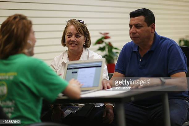 Elvira Lopezto and Pedro Salavarria Carrasco speak with Helen Alvarez an insurance agent from Sunshine Life and Health Advisors as they discuss plans...
