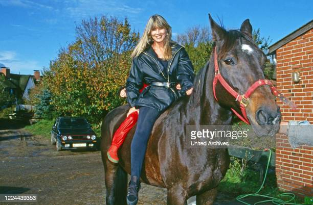 Elvira wife of German football player Guenter Netzer with daughter Alana on horseback at Sylt island Germany 1993
