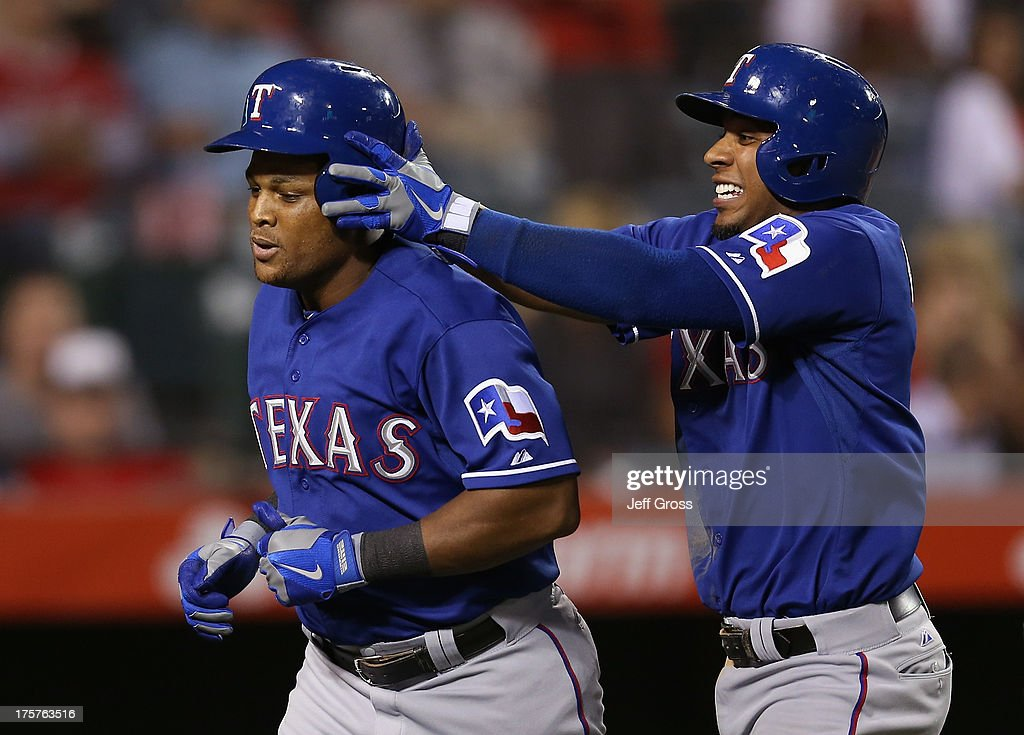 Elvis Andrus (R) #1 of the Texas Rangers celebrates a two-run home by Adrian Beltre (L) #29 by taking his helmet off in the sixth inning against the Los Angeles Angels of Anaheim at Angel Stadium of Anaheim on August 7, 2013 in Anaheim, California.
