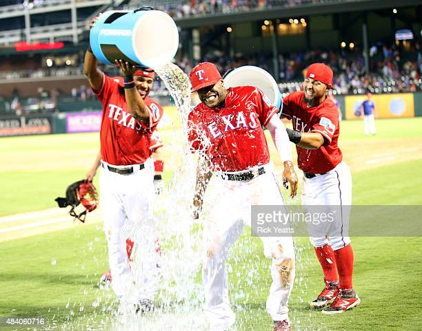 Elvis Andrus and Rougned Odor dump the coolers on Delino DeShields of the Texas Rangers after hitting his first major league home run against the...