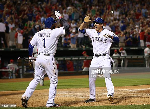 Elvis Andrus celebrates with Jim Adduci of the Texas Rangers as he scores the winning run on a walk on Shin-Soo Choo in the ninth inning against the...