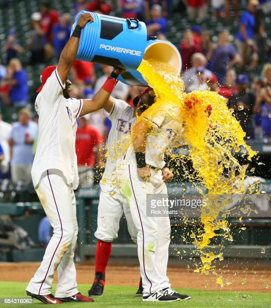 Elvis Andrus of the Texas Rangers and Rougned Odor celebrate Jared Hoying first major league home run with dumping the coolers on him at the end of...
