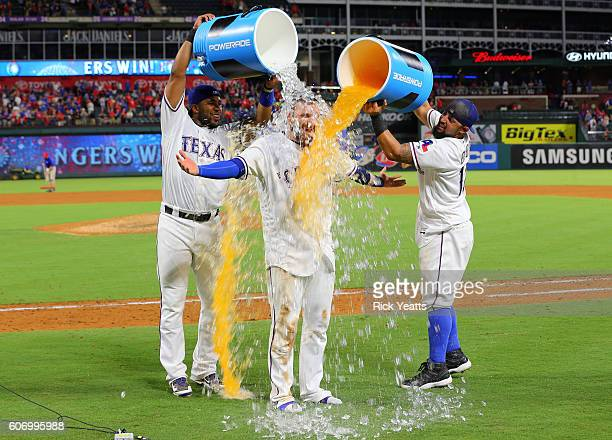 Elvis Andrus of the Texas Rangers and Rougned Odor celebrates by dumping the coolers on Jonathan Lucroy for hitting a two run walk off single against...