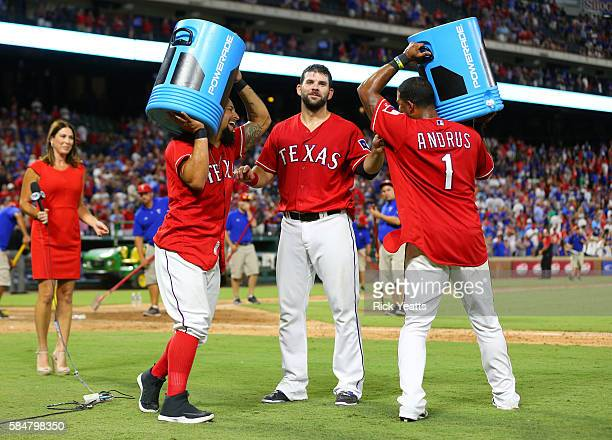 Elvis Andrus of the Texas Rangers and Rougned Odor circle Mitch Moreland with the coolers after Moreland walk off home run against the Kansas City...