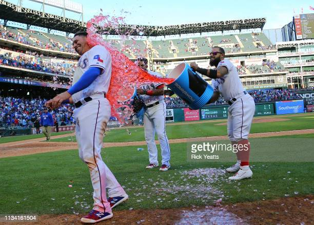 Elvis Andrus of the Texas Rangers and Rougned Odor dump the coolers of water on Asdrubal Cabrera celebrating the win against the Chicago Cubs at...