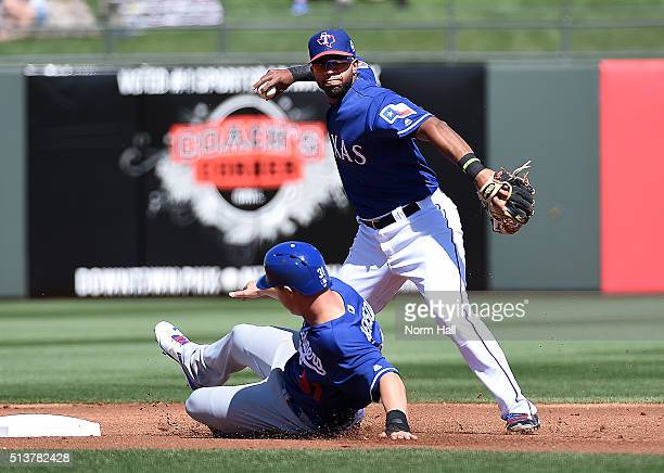 Elvis Andrus of the Texas Rangers attempts to turn a double play as Joc Pederson of the Los Angeles Dodgers slides into second base during the first...