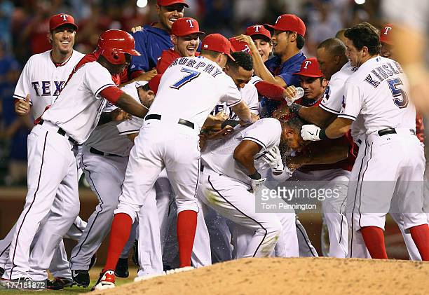 Elvis Andrus of the Texas Rangers celebrates with his team after hitting a sacrifice fly that allowed Adam Rosales of the Texas Rangers to score the...