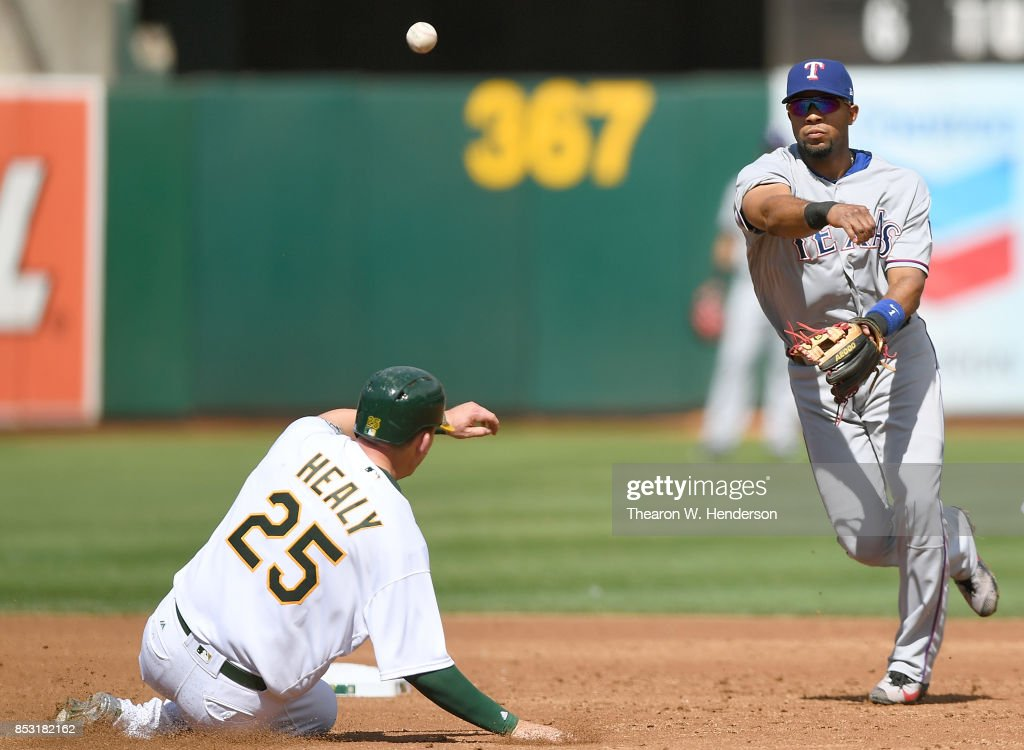 Elvis Andrus #1 of the Texas Rangers completes the double-play throwing over the top of Ryon Healy #25 of the Oakland Athletics in the bottom of the second inning at Oakland Alameda Coliseum on September 24, 2017 in Oakland, California.