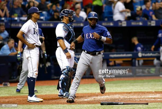Elvis Andrus of the Texas Rangers crosses home plate in front of catcher Wilson Ramos of the Tampa Bay Rays and pitcher Chris Archer to score off a...