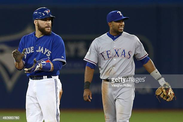 Elvis Andrus of the Texas Rangers is reacts as he is unable to catch the ball as Russell Martin of the Toronto Blue Jays slides into second safely in...
