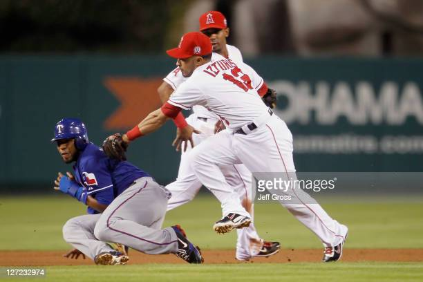 Elvis Andrus of the Texas Rangers is tagged out by second baseman Maicer Izturis of the Los Angeles Angels of Anaheim after being caught in a run...