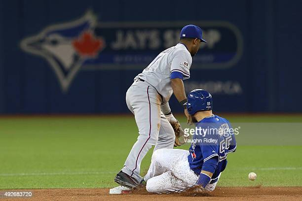 Elvis Andrus of the Texas Rangers is unable to catch the ball as Russell Martin of the Toronto Blue Jays slides into second safely in the seventh...