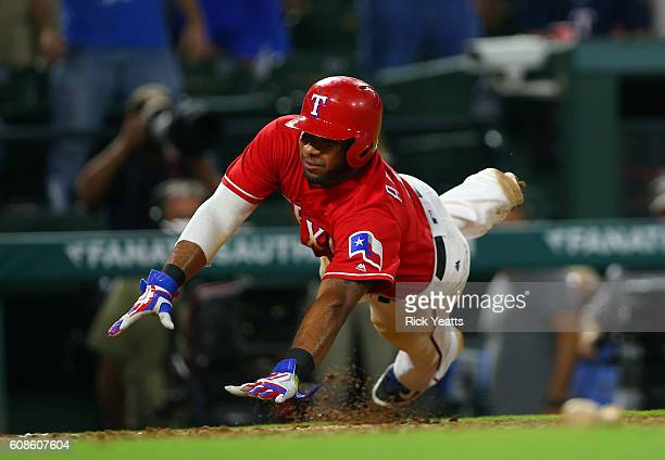 Elvis Andrus of the Texas Rangers slides in to score in the ninth inning to end the game against the Los Angeles of Angels Anaheim at Globe Life Park...