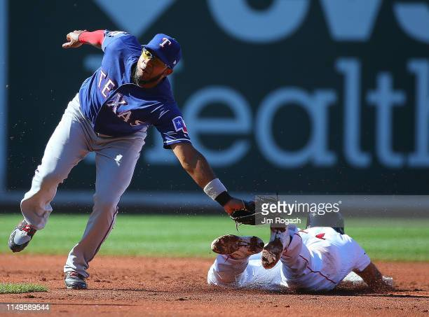 Elvis Andrus of the Texas Rangers tags out Rafael Devers of the Boston Red Sox trying to steal second base in the second inning at Fenway Park on...