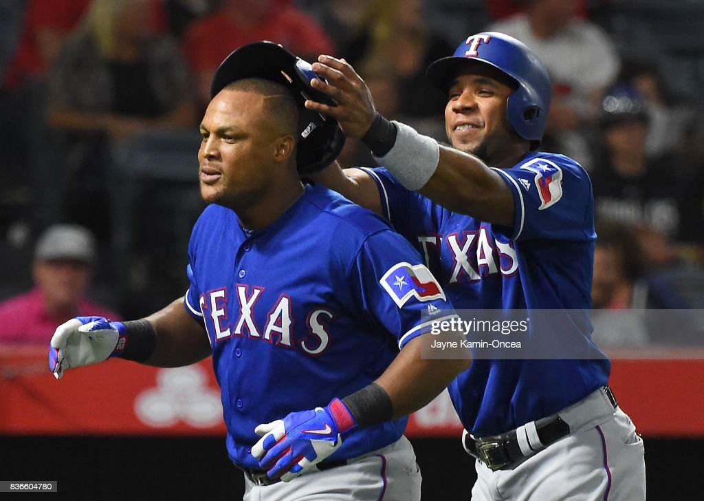 Elvis Andrus #1 of the Texas Rangers takes the helmet of Adrian Beltre #29 as he heads to the dugout after a three run home run in the third inning of the game against the Los Angeles Angels of Anaheim at Angel Stadium of Anaheim on August 21, 2017 in Anaheim, California.