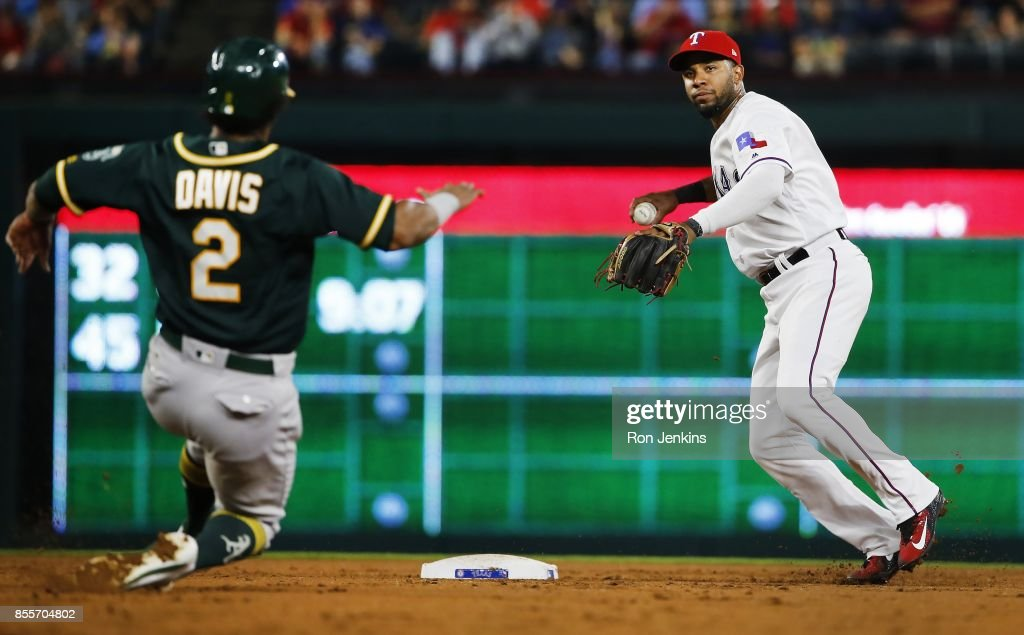 Elvis Andrus #1 of the Texas Rangers throws to first base on a double play as Khris Davis #2 of the Oakland Athletics slides to second base during the second inning at Globe Life Park in Arlington on September 29, 2017 in Arlington, Texas.