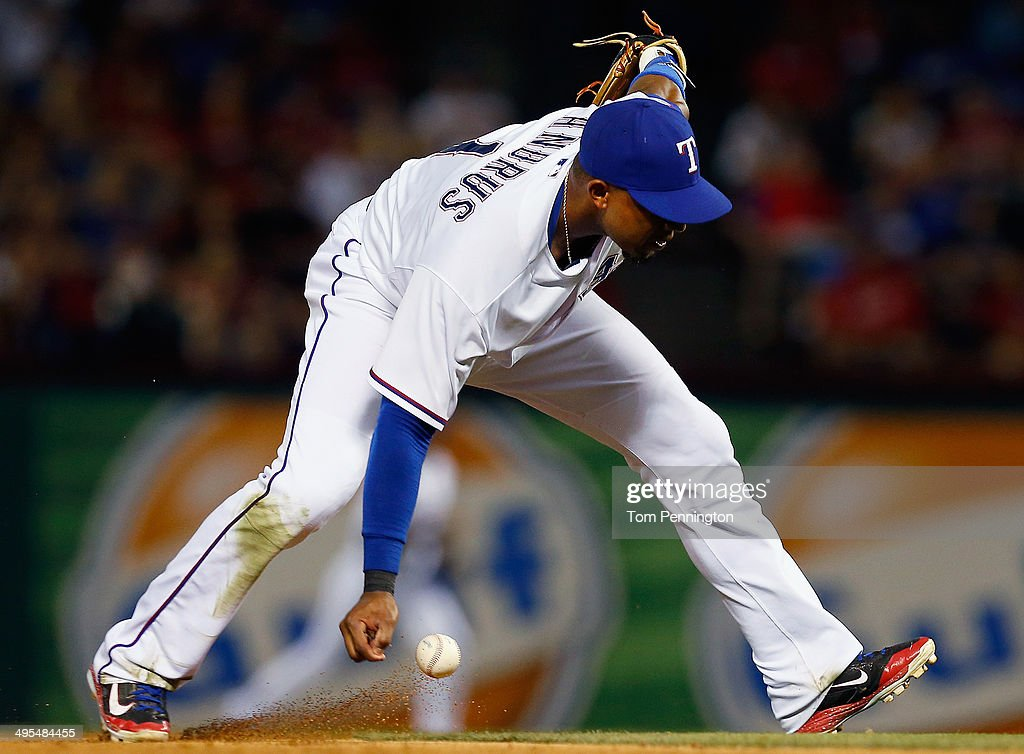 Elvis Andrus #1 of the Texas Rangers tries to bare hand an infield single hit by Manny Machado #13 of the Baltimore Orioles in the top of the eighth inning at Globe Life Park in Arlington on June 3, 2014 in Arlington, Texas.