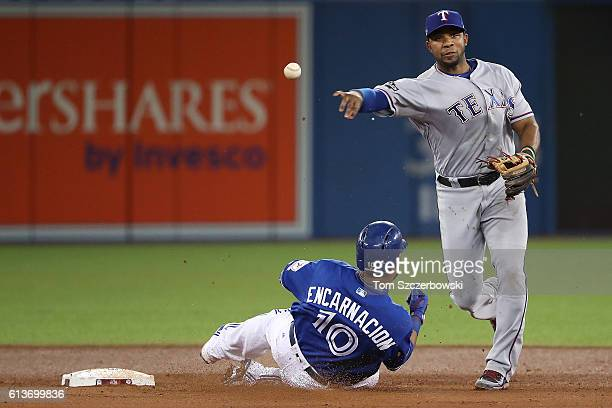 Elvis Andrus of the Texas Rangers turns a double play over Edwin Encarnacion of the Toronto Blue Jays for the final two outs of the fifth inning...