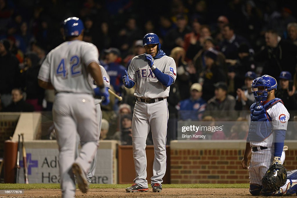 Elvis Andrus of the Texas Rangers (C) waits at home plate for teammate Adrian Beltre as catcher Welington Castillo of the Chicago Cubs kneels on the field after Beltre hit a two-run home run scoring Andrus in the eighth inning at Wrigley Field on April 16, 2013 in Chicago, Illinois. All uniformed team members are wearing jersey number 42 in honor of Jackie Robinson Day.