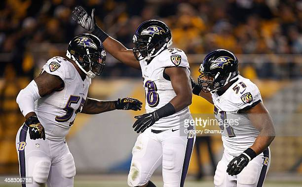 Elvis Dumervil celebrates with Terrell Suggs and Daryl Smith of the Baltimore Ravens after sacking Ben Roethlisberger of the Pittsburgh Steelers...