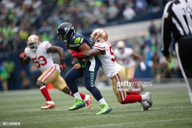 Elvis Dumervil of the San Francisco 49ers hits Russell Wilson of the Seattle Seahawks during the game at CenturyLink Field on September 17 2017 in...