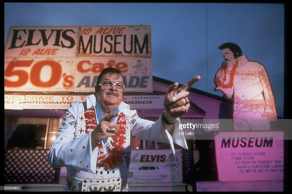 Elvis impersonator Bill Beeny wearing a white bejeweled jumpsuit while standing outside his Elvis Is Alive Museum in Wright City, Missouri.