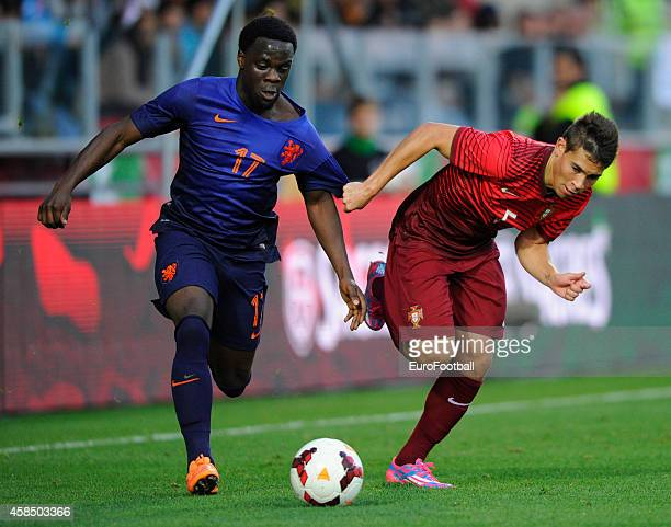 Elvis Manu of the Netherlands is tackled by Raphael Guerreiro of Portugal during the UEFA U21 Championship second leg playoff between Portugal and...