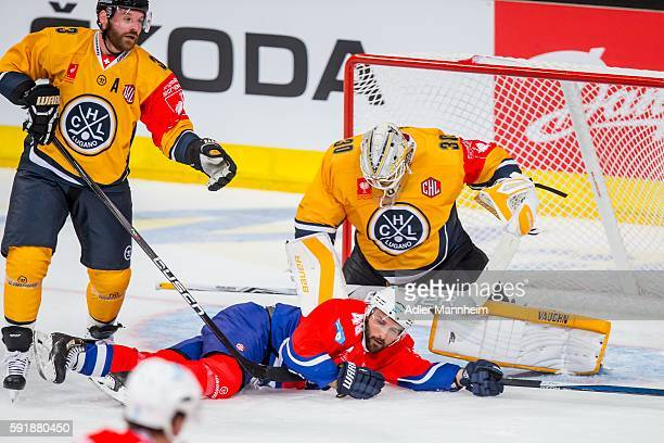 Elvis Merzlikins of HC Lugano and Jamie Tardif of Adler compete for control of the puck during the Champions Hockey League match between Adler...