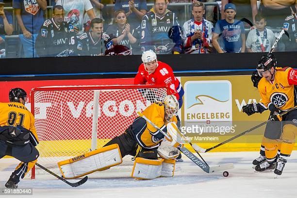 Elvis Merzlikins of HC Lugano David Wolf of Adler and Alessandro Chiesa of HC Lugano compete for the puck during the Champions Hockey League match...