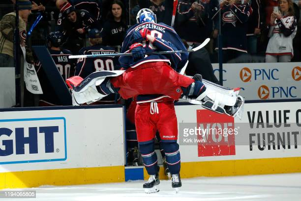 Elvis Merzlikins of the Columbus Blue Jackets is congratulated by Nick Foligno after defeating the Carolina Hurricanes on January 16 2020 at...