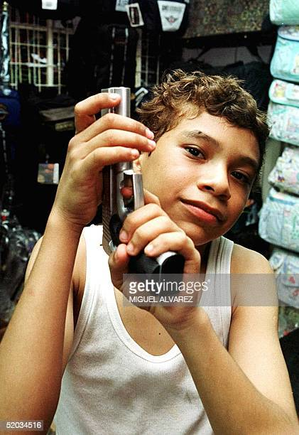 Elvis Peralta age 12 handles a toy gun that he bought for two dollars in a local market September 22 1999 Elvis Peralta de 12 anos manipula una...