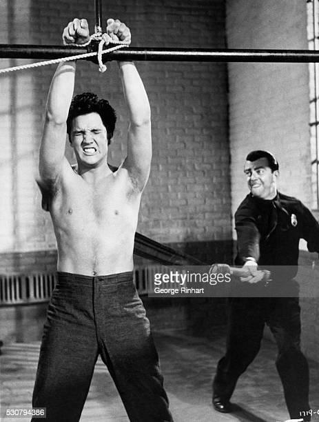 1957 Elvis Presley after participating in a prison riot grimaces as he suffers the severe punishment dealt out by guard Bill Hickman 'Jailhouse Rock'...