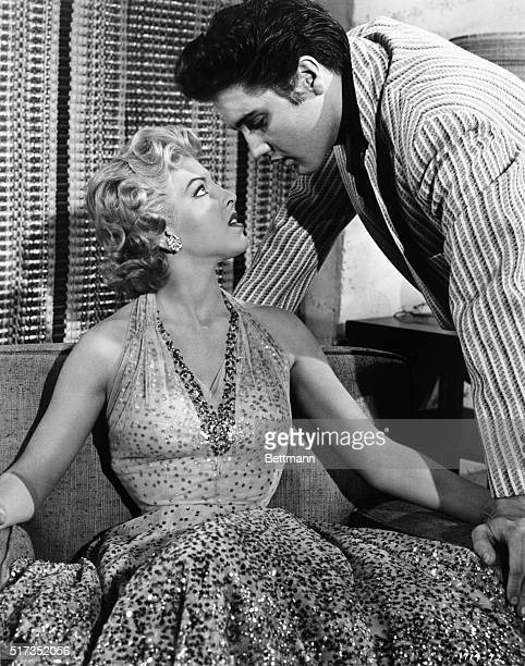 Elvis Presley and actress Ann Neylan in a scene from the Avon Production Jailhouse Rock She is seated in a loveseat as the rock and roll star hovers...