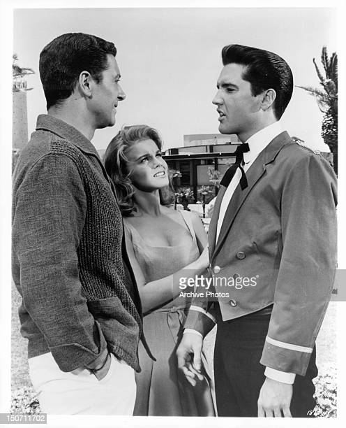 Elvis Presley explains to Cesare Danova and AnnMargret that he has taken a job as a waiter to earn money to buy a new racecar engine in a scene from...