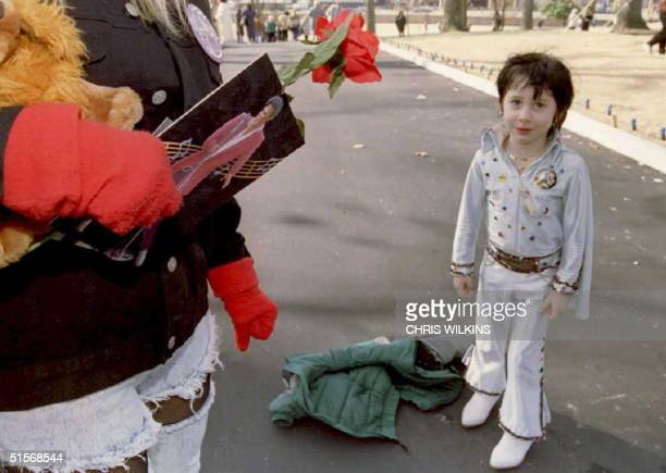 Elvis Presley fan Dawn Smyth holds a rose and a picture of the late singer as she talks to fiveyearold Elvis impersonator Kyle Selig of Tacoma...