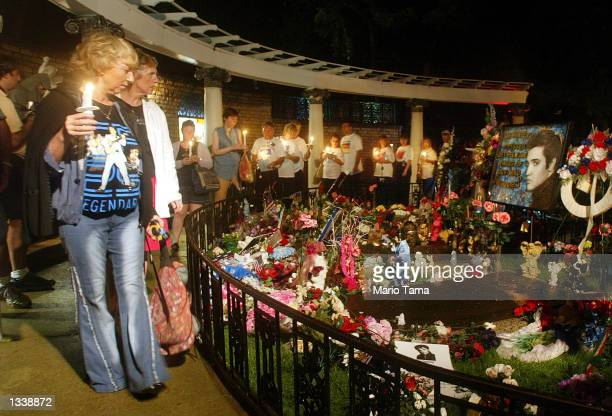 Elvis Presley fans file past his grave during a candlelight vigil at Graceland marking the 25th anniversary of Presley's death during Elvis Week...