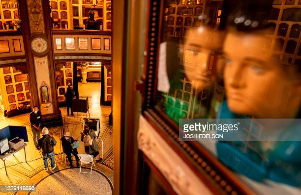Elvis Presley figurines are seen inside a memorial compartment as voters fill out their ballots at a polling station at the San Francisco Columbarium...