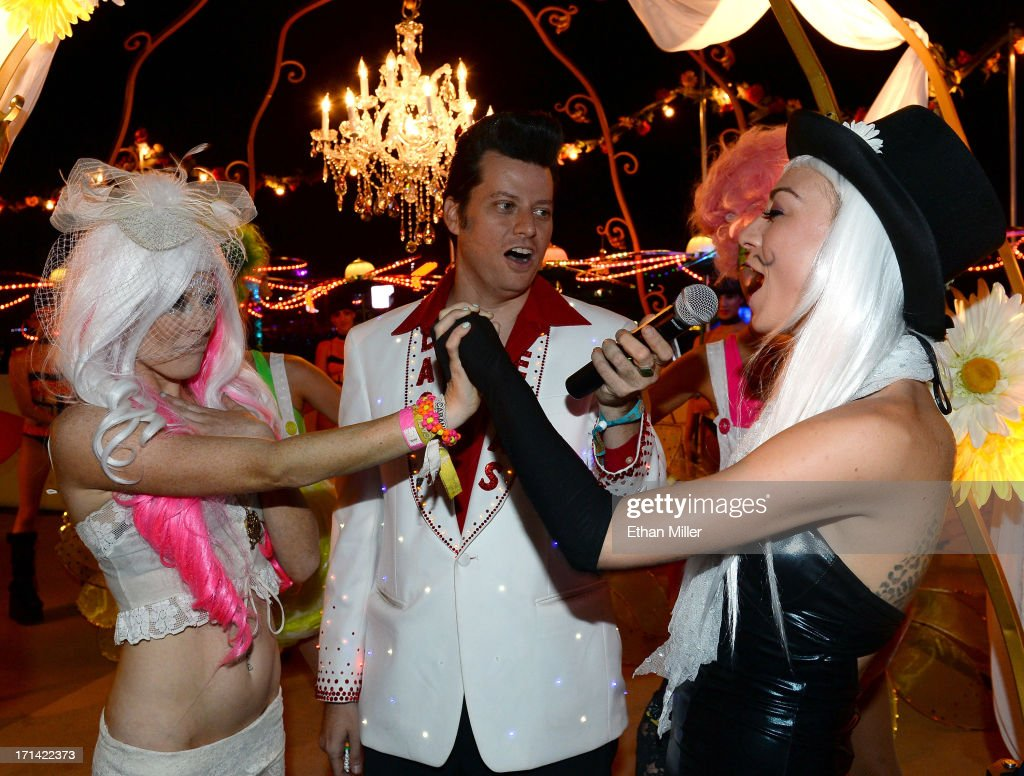 Elvis Presley impersonator Brian Mills (C) performs a commitment ceremony for Jessica O'Donnell (L) and Adele Vannini (R) at the 17th annual Electric Daisy Carnival at Las Vegas Motor Speedway on June 23, 2013 in Las Vegas, Nevada.