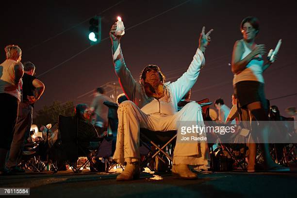 Elvis Presley impersonator Dennis Nickells from New York attends a vigil in memory of the late Elvis Presley outside the front gates of Graceland...