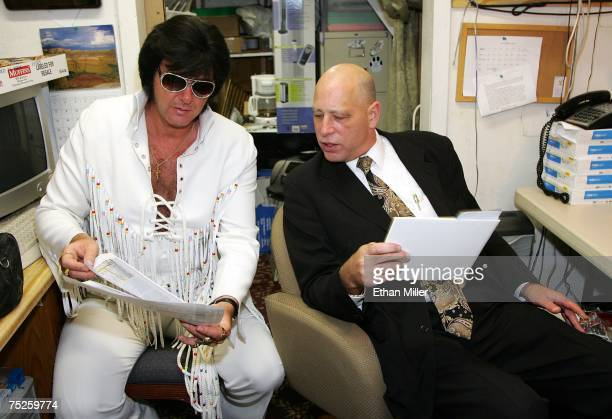 Elvis Presley impersonator Jeff Stanulis and the Rev Rob Hickey look at news reports on 7/7/07 weddings during a quick break in performing marriage...