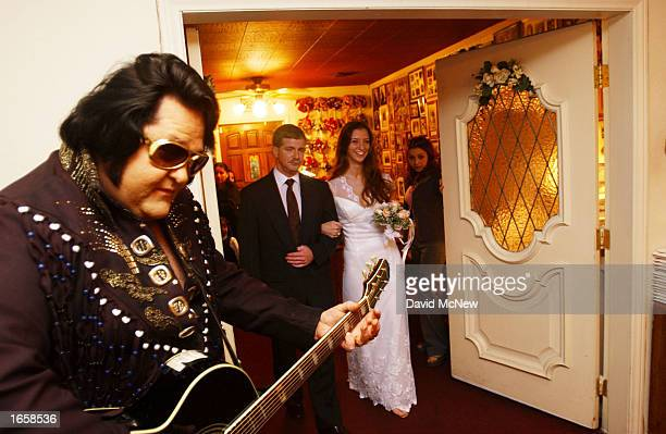 Elvis Presley impersonator Norm Jones plays guiter as Bruce Barnett of Virginia Beach Virginia escorts his daughter Gayle to her wedding ceremony at...