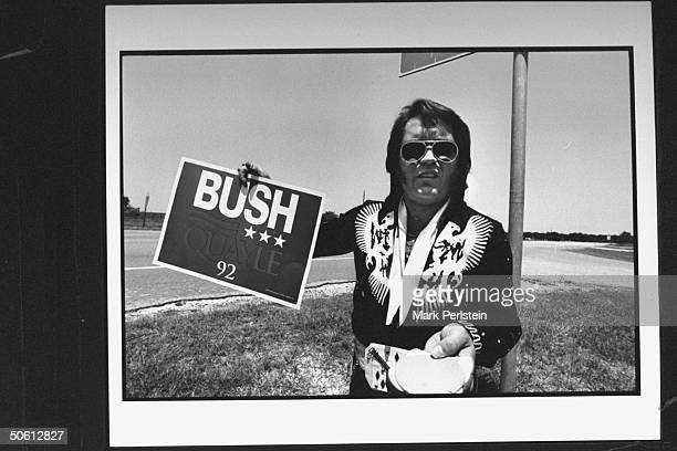 Elvis Presley impersonator sporting sunglasses Elvistype jumpsuit as he holds up a BUSH '92 campaign sign a piece of bread w a slice of bologna on it...