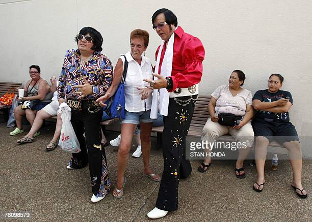 Elvis Presley impersonators Carl Cassady and Jim Schmidt pose with a woman 14 August 2007 at Graceland the home of Presley in Memphis Tennessee Fans...