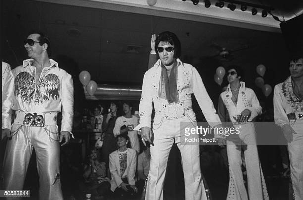 Elvis Presley impersonators competing in the Elvis Olympics eventual overall winner Mike Albert in white sunglasses looking much like the other...