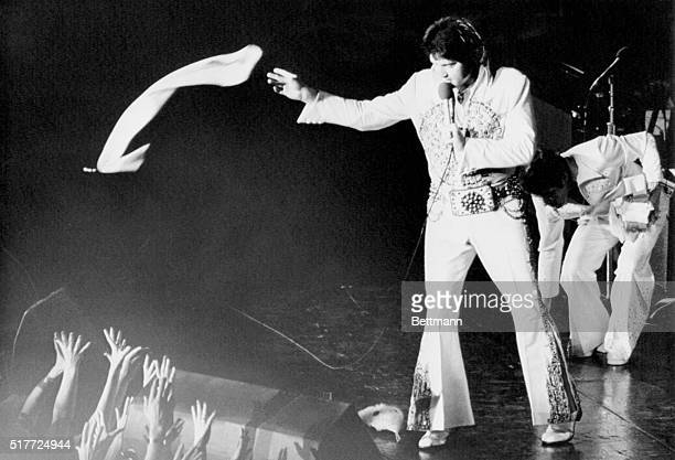 Elvis Presley, in a white jumpsuit with gold brocade and studs, tosses a nylon scarf into the waiting hands of the fans at a concert in the...