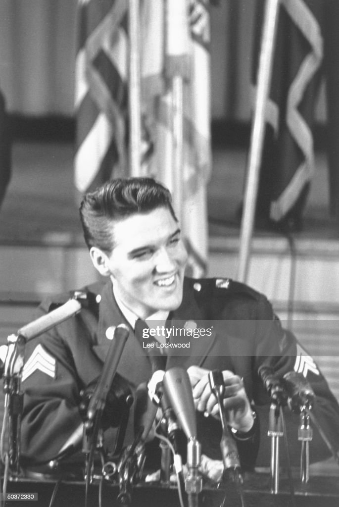 Elvis Presley in uniform at press conference on his last day serving in the US Army.